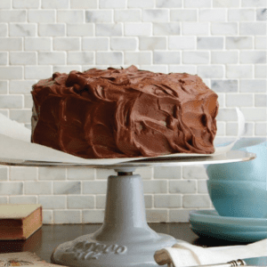 close up of cake with chocolate frosting on white cake stand in kitchen