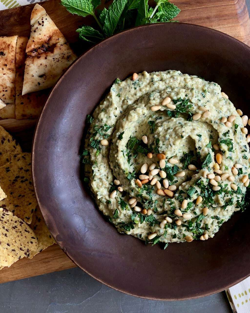 grilled zucchini baba ganoush in brown bowl and topped with pepitas and parsley