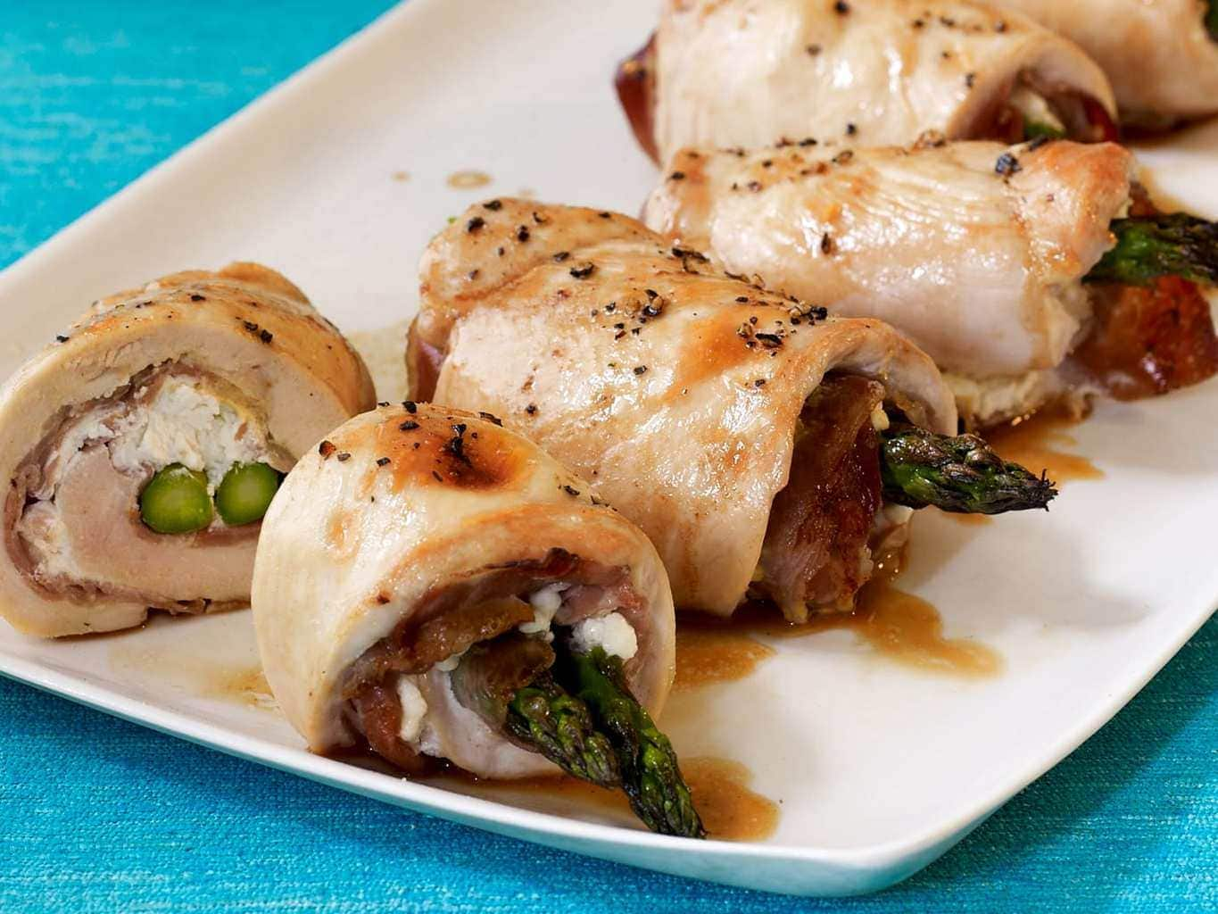 chicken and asparagus roll ups cut into on a plate