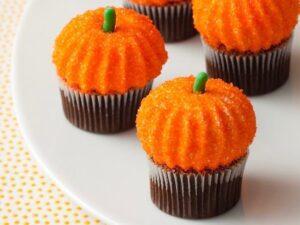pumpkin marshmallows on cupcakes on white plate