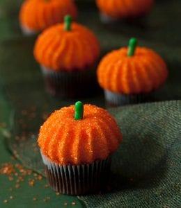 pumpkin marshmallows on cupcakes on green background
