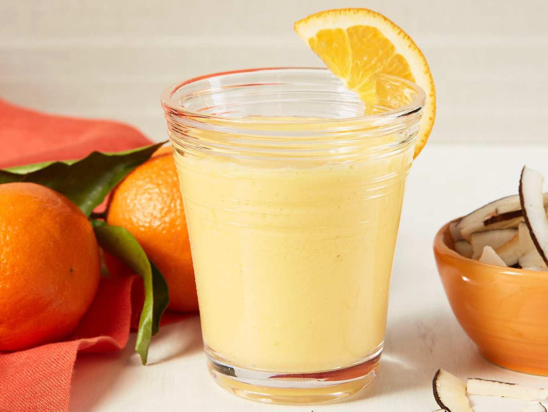 A mango smoothie with an orange wedge