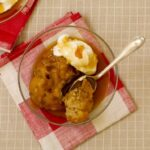 apple dumplings in a bowl with cream and cider sauce