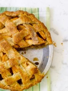 apple pie with pecan streusel on green linen overhead