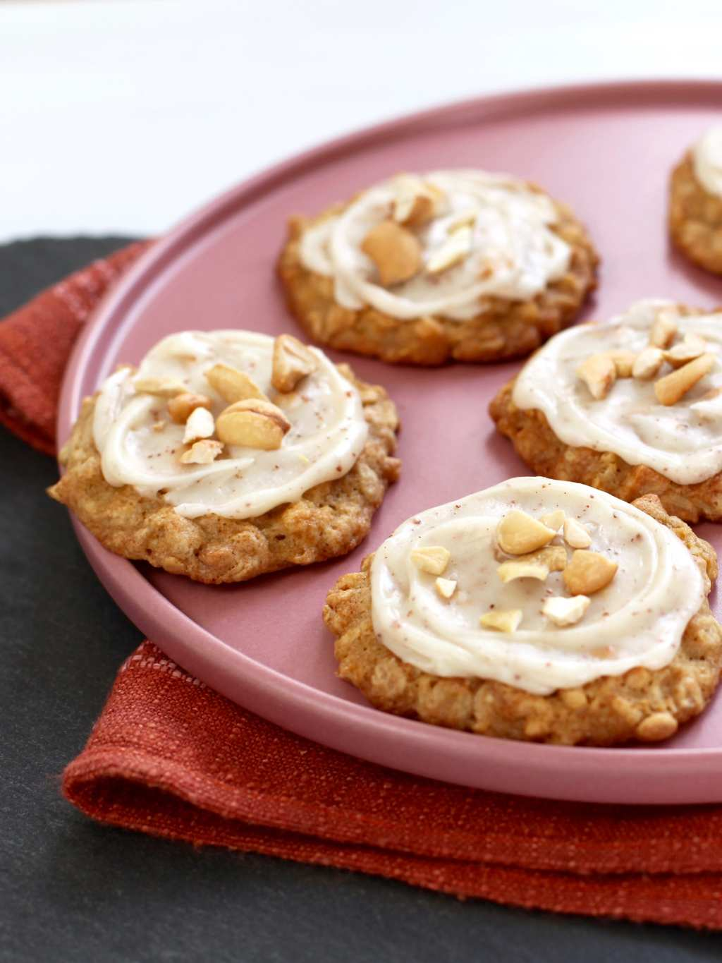 Cashew Cookies with Brown Butter Frosting on a pink plate close crop