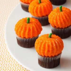 Pumpkin marshmallows on cupcakes with green stems