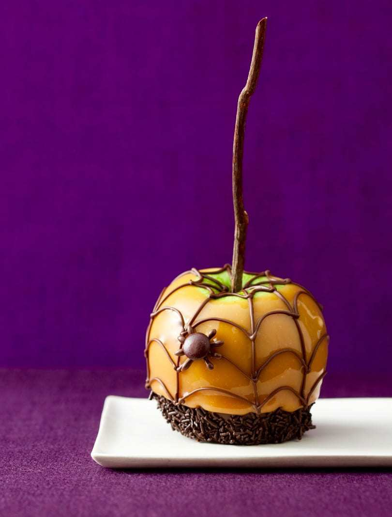 Single Halloween caramel apple on purple linen