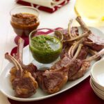 baby lamb chops on white plate with green and red sauces