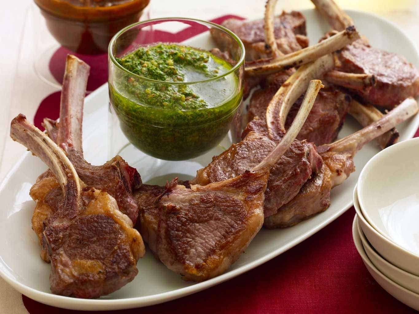Lamb Chops with red and green sauce on oval white plate, red linen