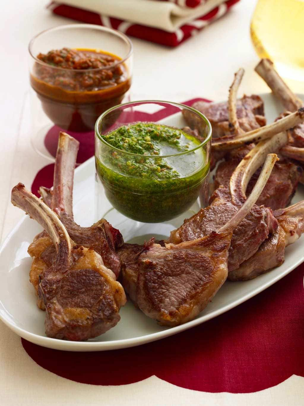 Baby lamb chops with red and green sauce on white oval platter, red linen