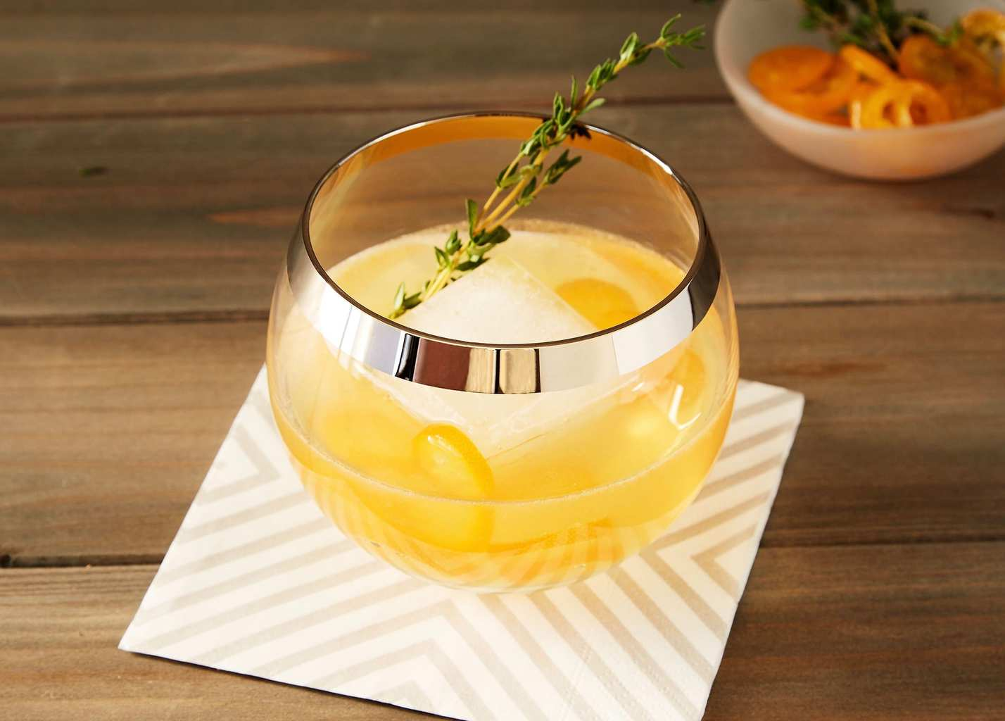 Kumquat Thyme Cocktail in gold-rimmed glass with thyme sprig on wood and striped napkin