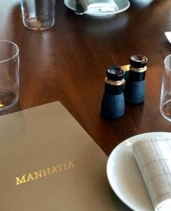 Manhatta menu on table with binoculars