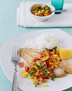 broiled fish with mango salsa on a plate with rice