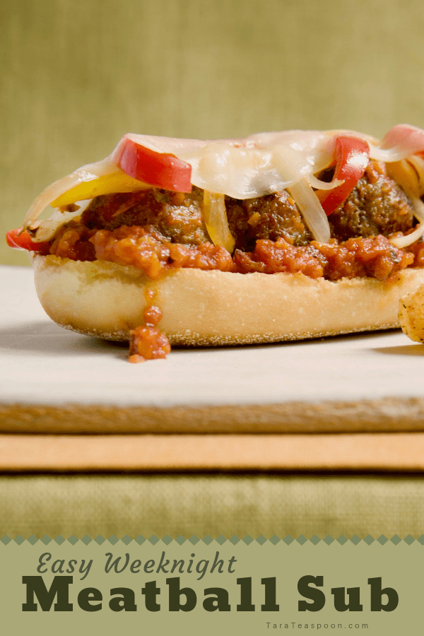 A delicious open face meatball sub on a cutting board pin