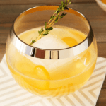 Glass of a Thyme Cocktail with kumquat and bourbon on striped cocktail napkin