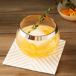Kumquat Thyme Cocktail with bourbon on striped cocktail napkin