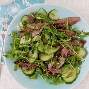 close up of Ginger Beef Salad with Asian Dressing on light blue plate