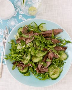 Ginger Beef Salad with Asian Dressing on light blue plate