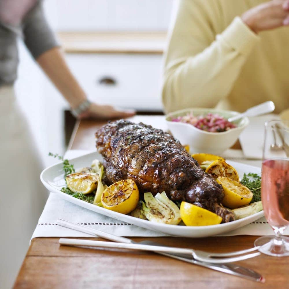 roast leg of lamb on platter with lemons