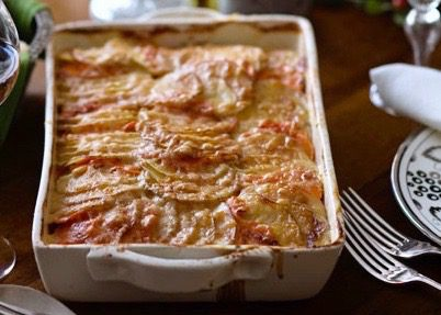 golden carrot and potato gratin in a dish