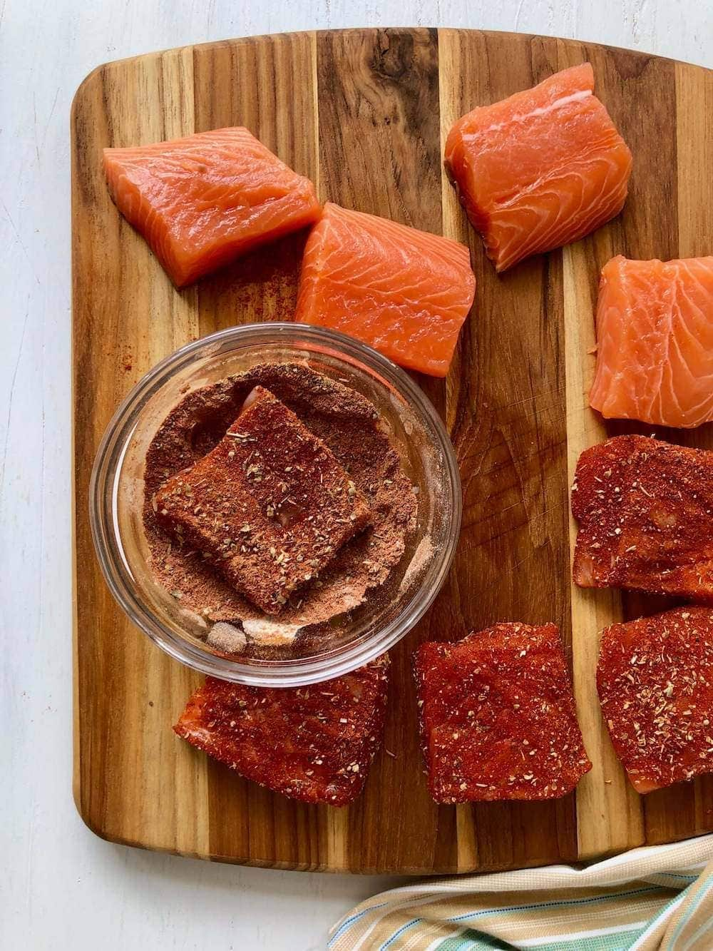 salmon with spices and rub on cutting board