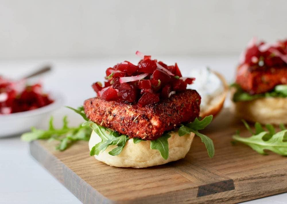 Blackened salmon sliders on a cutting board with beet relish