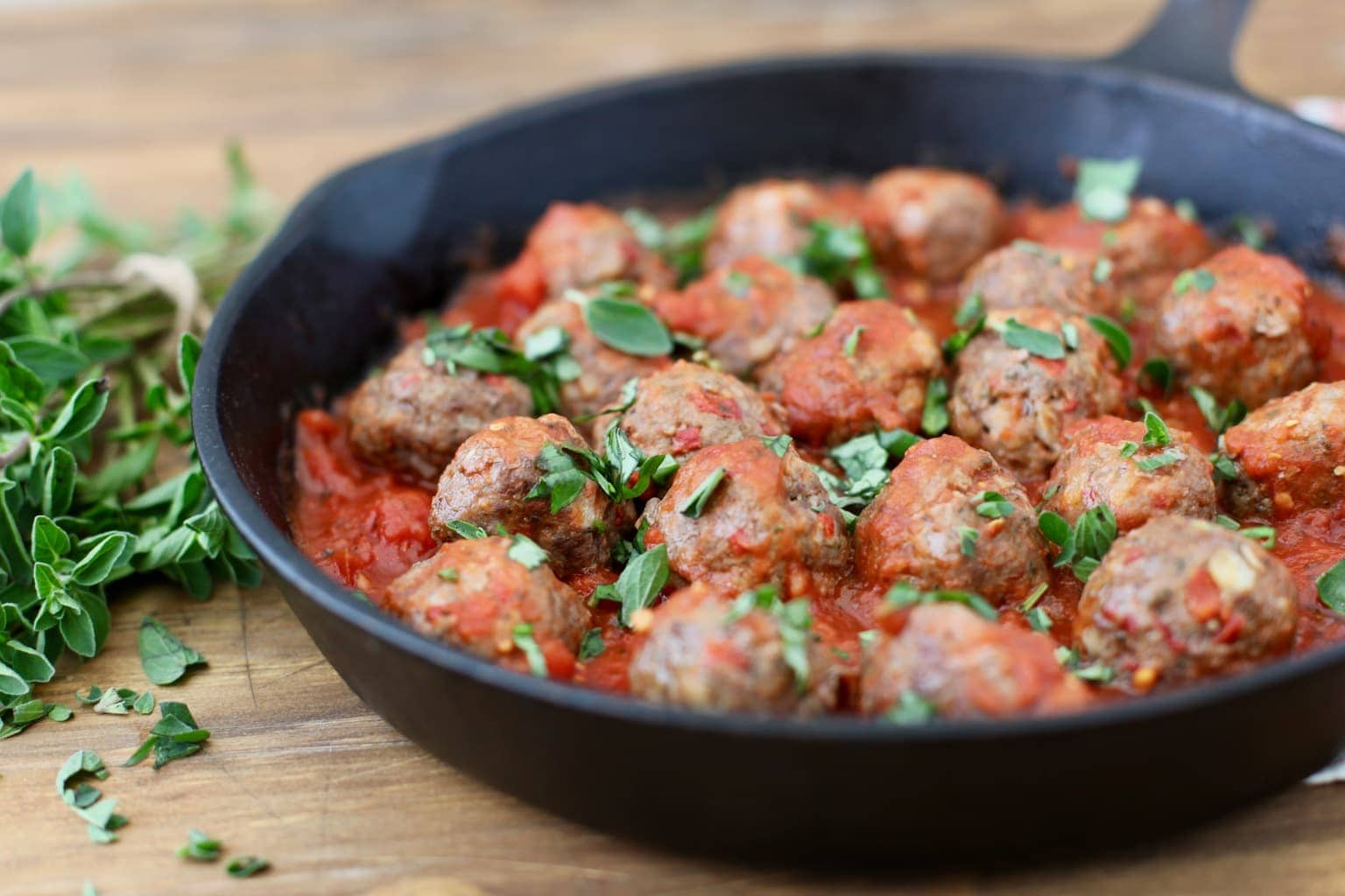 italian meatballs in cast iron skillet with herbs