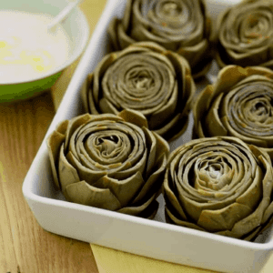 artichokes with lemon mayo in white casserole dish