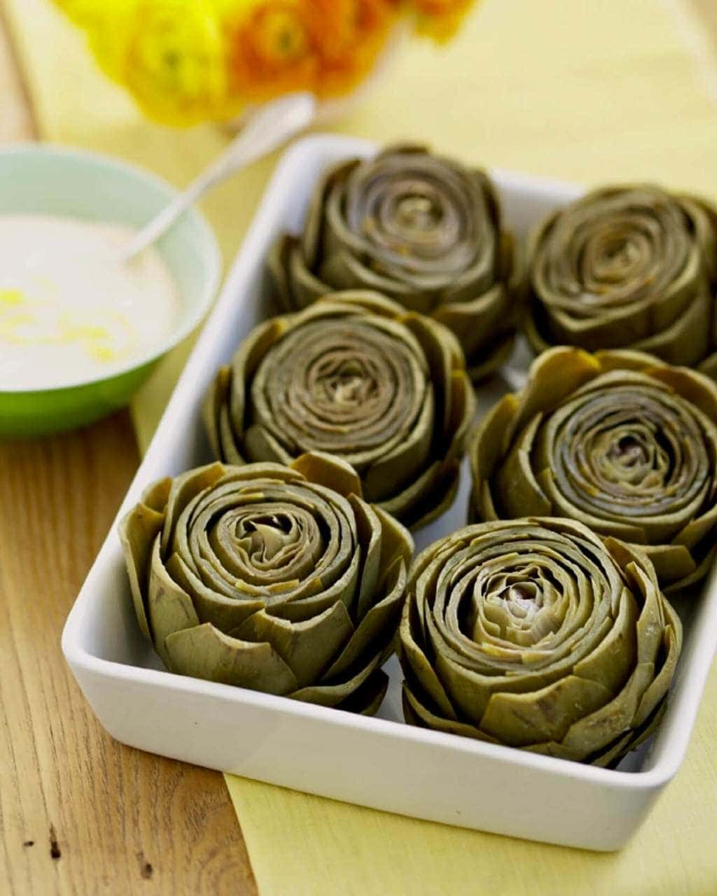 cooked artichokes in dish with dip