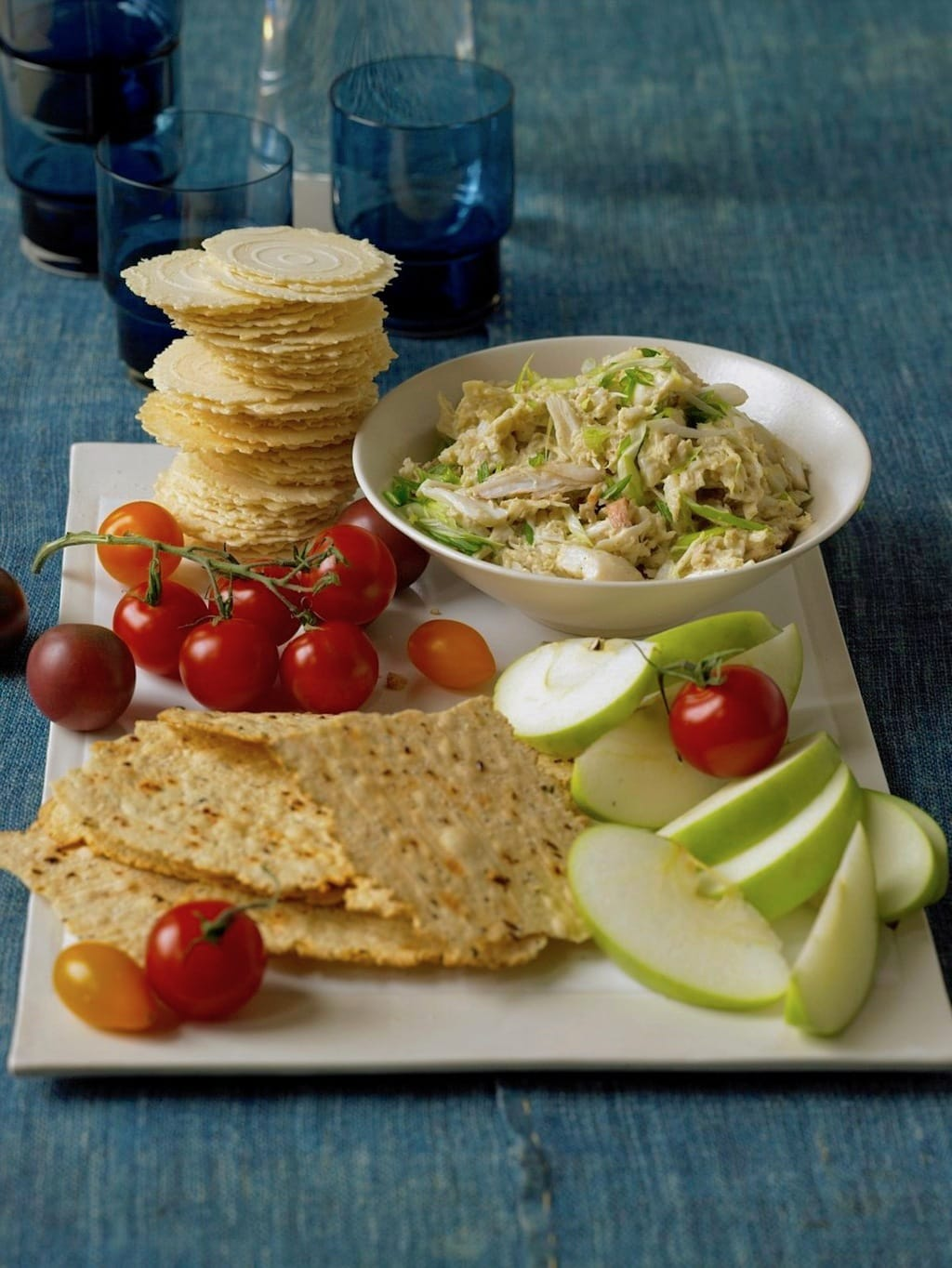 Crab dip with crackers, veggies, fruit on white tray