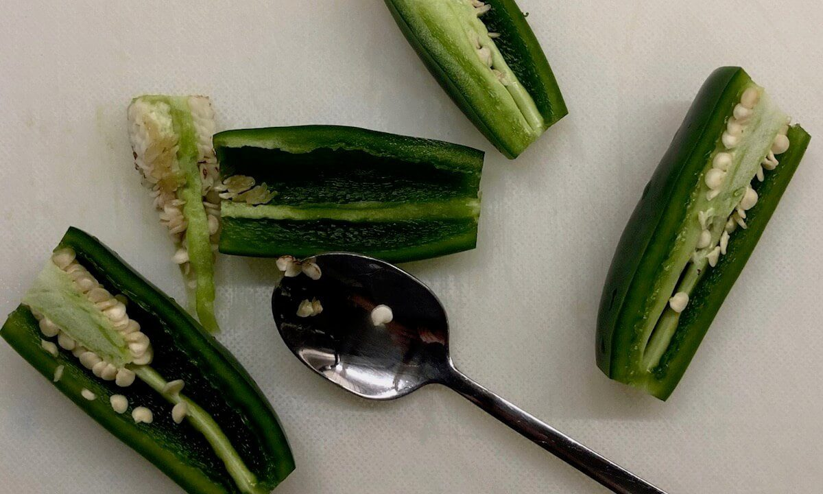 jalapeno peppers being sliced and de-seeded