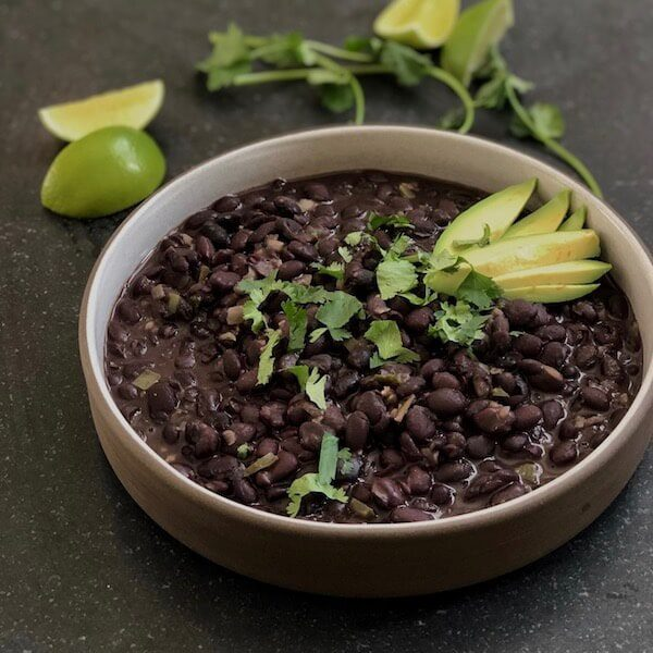 creamy black beans in a bowl with cilantro, lime and avocado fixings