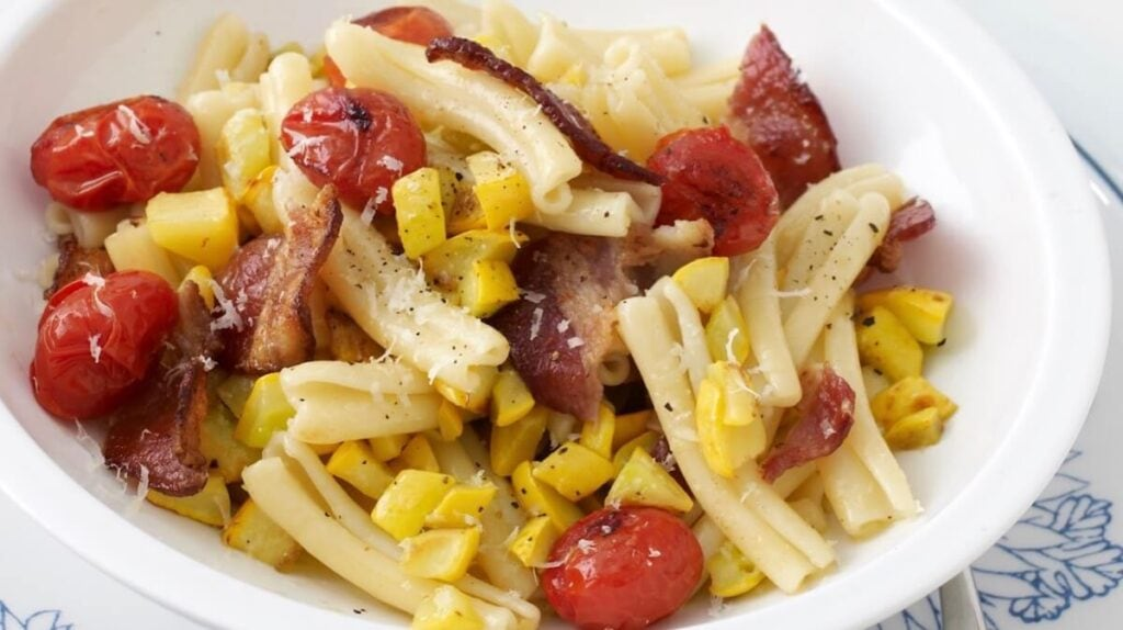 pasta with tomatoes bacon and yellow squash on blue plate