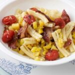 Pasta with tomatoes, bacon and yellow squash in white bowl