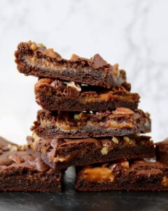 caramel chocolate brownies with pecans in a stack