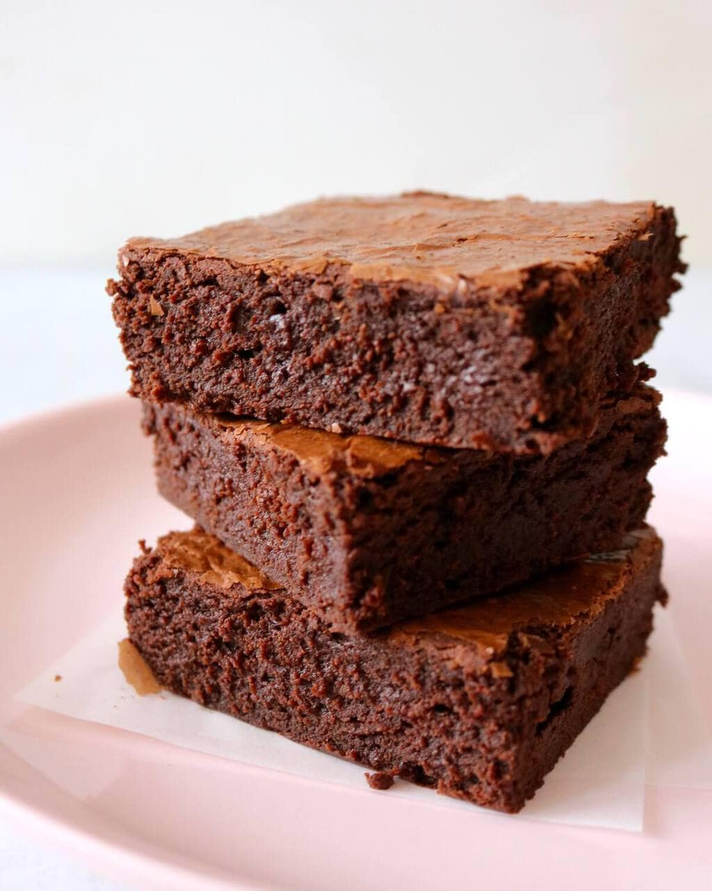 Stack of three brownies on pink plate