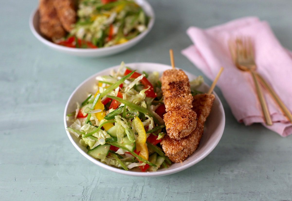 horizontal shot of sesame chicken and ginger cole slaw w pink napkin