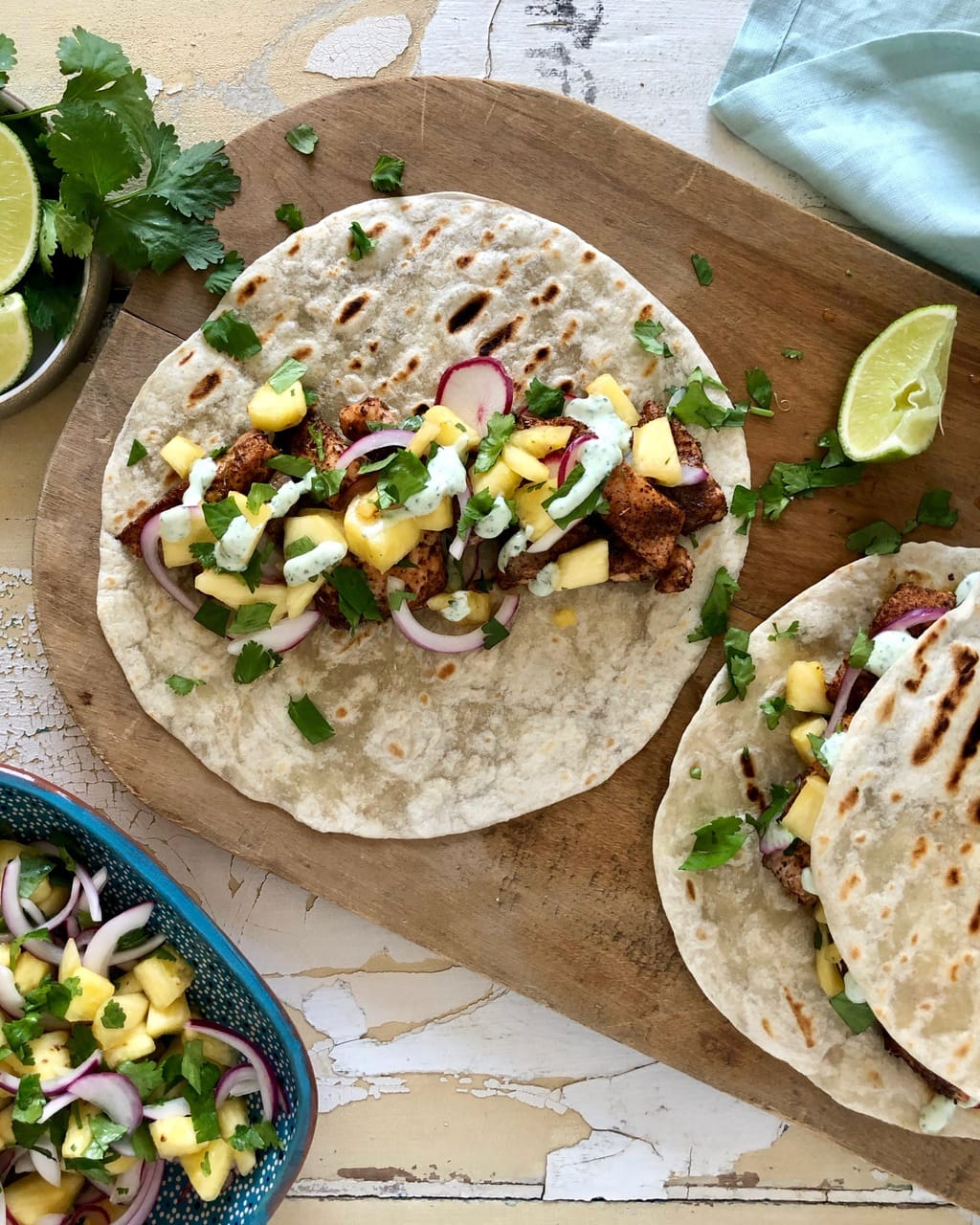 tacos with cilantro, lime wedges, and bowl of pineapple salsa