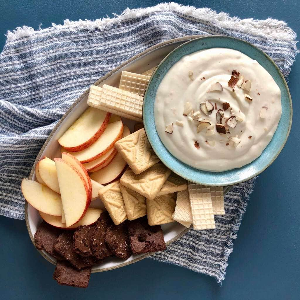 Fruit dip with apples and cookies on blue linen and blue surface