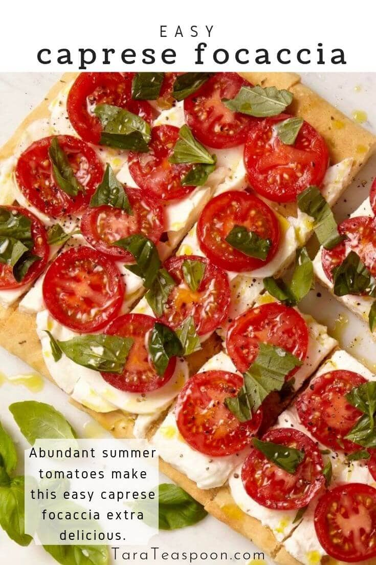 Caprese focaccia slice with tomatoes, basil and mozzarella drizzled with olive oil.