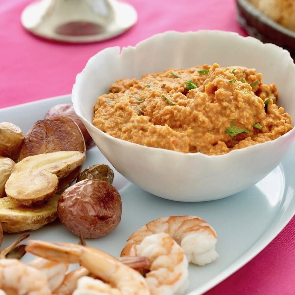 Romesco dip in a white bowl with shrimp and potatoes