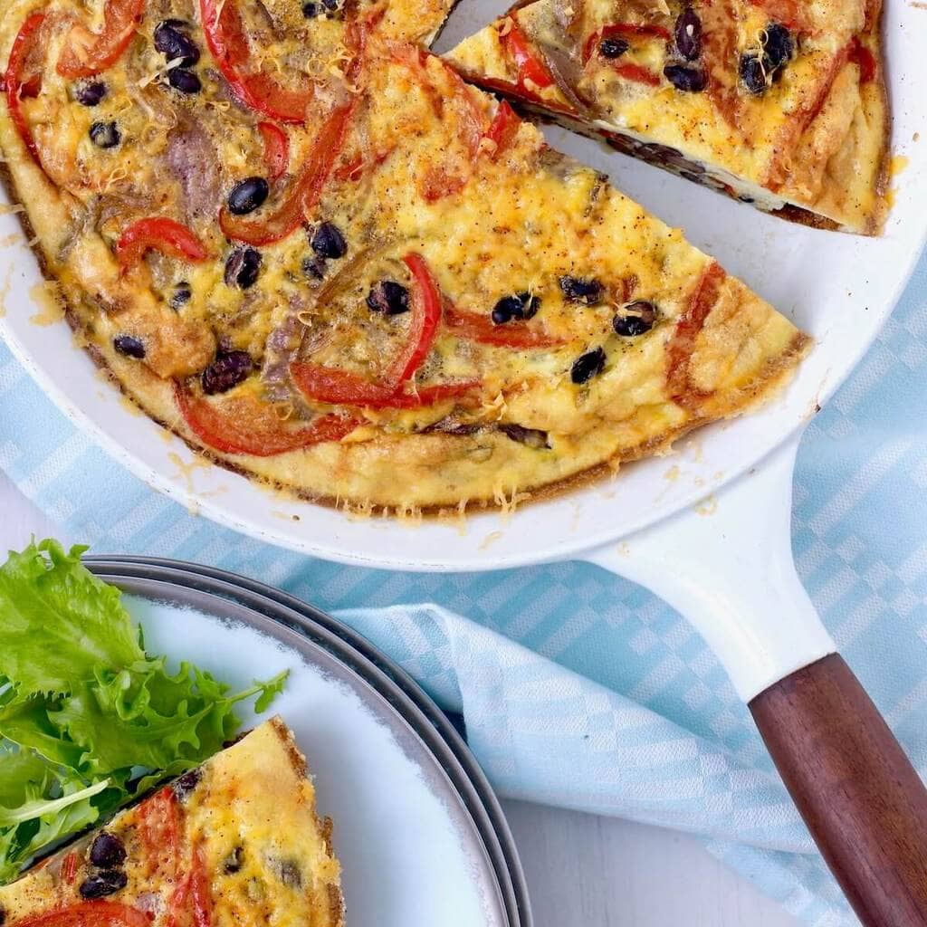 Frittata in white skillet with serving and lettuce
