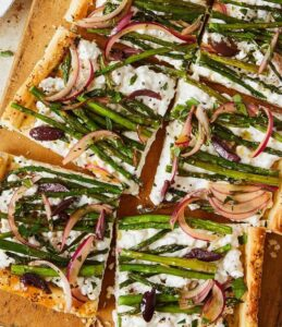 cottage cheese and asparagus puff pastry tart on a board