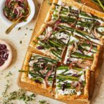 asparagus tart cut into squares with bowl of red onion dressing