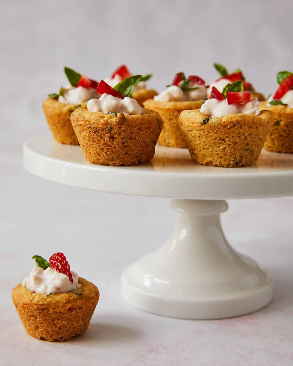 Soft basil sugar cookie cups with strawberry cottage cheese on a cake stand
