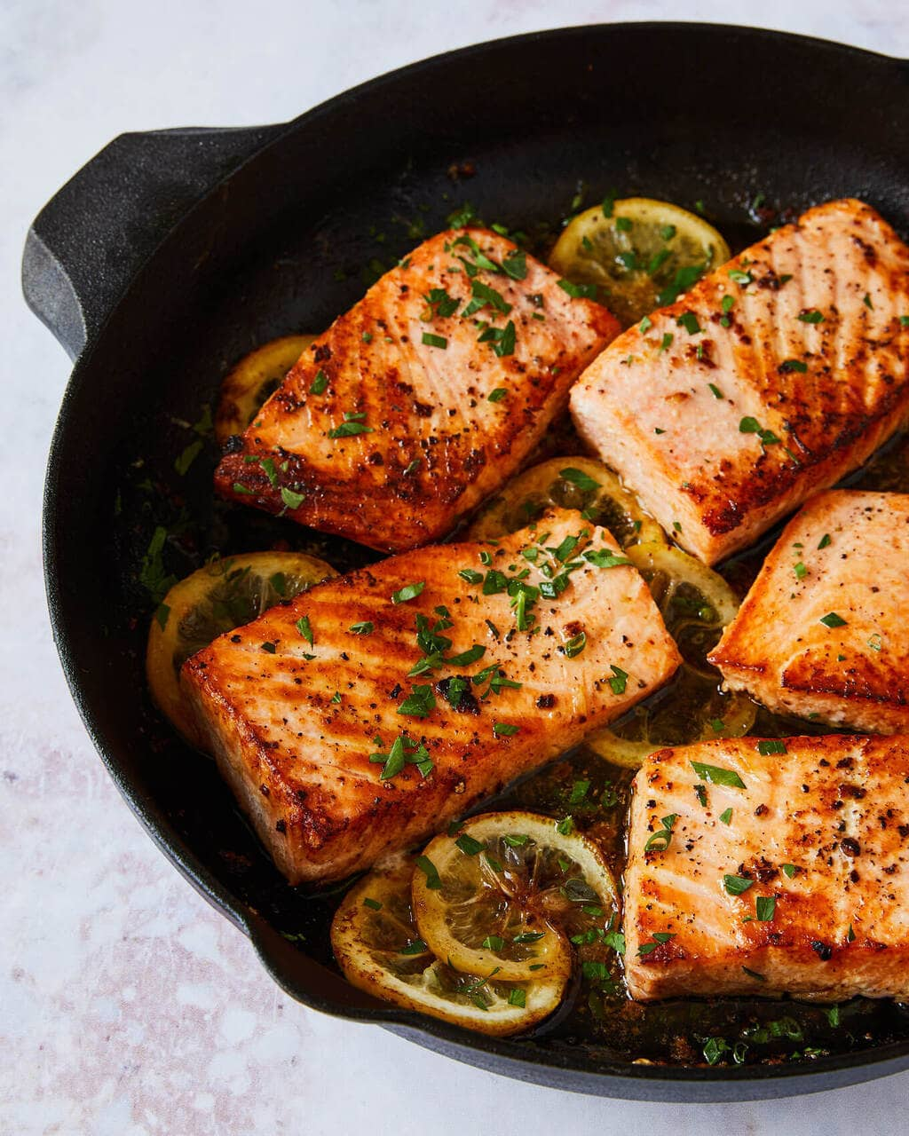 salmon cooking in a cast iron pan with lemon and herbs