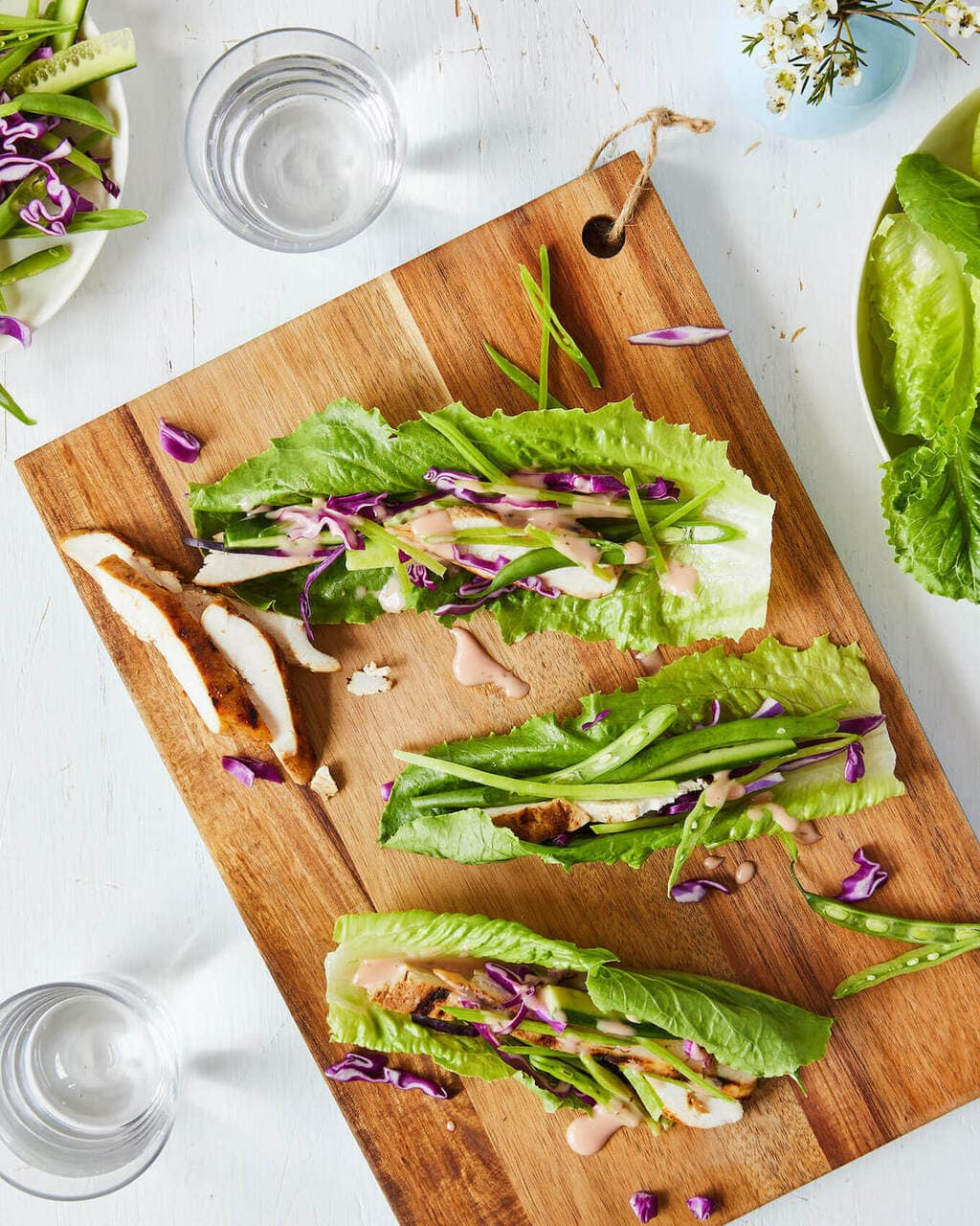 Grilled chicken lettuce wraps on a cutting board with glasses