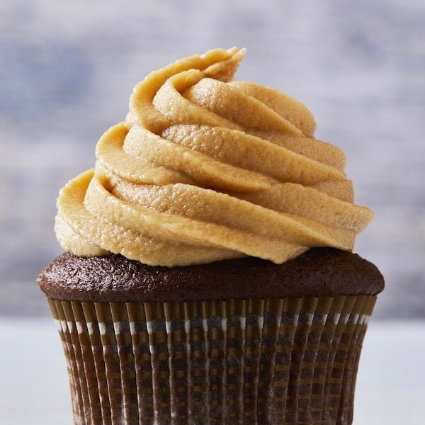 Peanut Butter Frosting swirled on Chocolate cupcake in brown and white striped paper baking cup