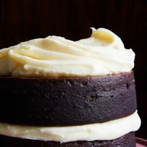 White cream cheese frosting on dark chocolate cake