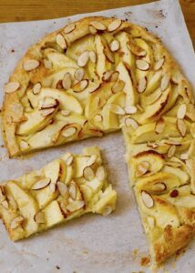 apple tart with sliced almonds on parchment